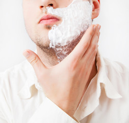 Young man with foam shaving his beard off with an electric shave