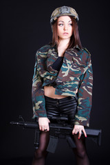 Woman in the military uniform with an assault rifle