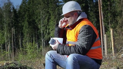 Lumberjack with money talking on the cell phone in forest