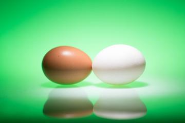 Braunes und weißes rohes Ei vor grünem Hintergrund