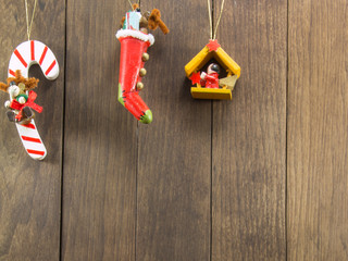 three christmas hunged decorations on wooden background