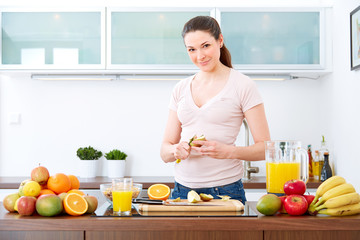 Young woman in the kitchen prepare fruits for breakfast.