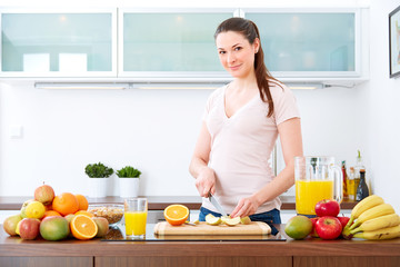 Young woman in the kitchen prepare fruits for breakfast. III