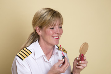 Female airline pilot applying lipstick makeup