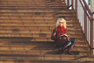 Young girl in leather coat with book seat on stairs bridge in su