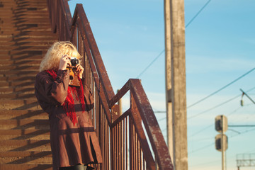 Young girl in leather coat with camera make photo on stairs brid