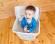 Smiling one year old boy getting out from garbage can