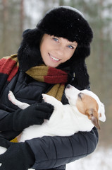 Young woman holding Jack Russell terrier in winter time