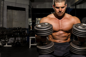 Man exercising with weights in dramatic lighting.