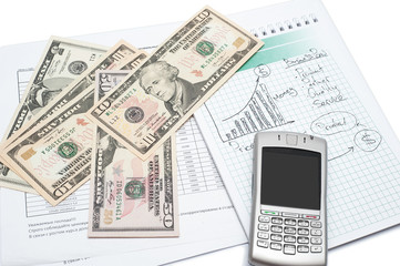 Cellphone and money on a notepad. Background image for finance