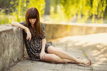 Outdoor portrait of a sad teenage girl in dress on floor