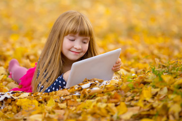 Little girl laying on grass and leaf and playing tablet pc