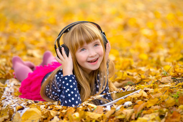 Young fashion girl with headphones an tablet pc lying at yellow