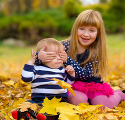 Cute funny children are playing in autumn park