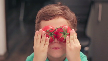little boy plays with tomatoes