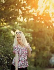 Spring woman in summer dress walking in green park enjoying the