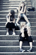 Group of happy teen girls sitting on the steps