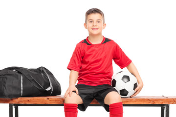 Little boy holding a soccer ball seated on a bench
