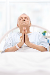 Male patient lying in hospital bed and praying to god