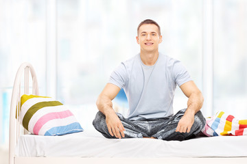 Young man in pajamas sitting on a bed