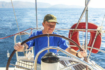 Man skipper at the helm controls sailing yacht.