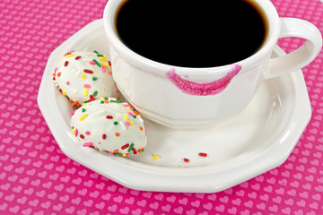 pink lipstick mark on coffee cup with cookies