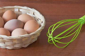 Яйца в корзинке и венчик на столе