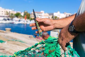 Majorca Cala Ratjada fisherman sewing fishing net