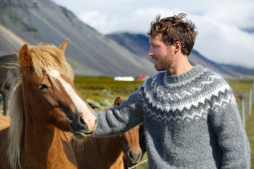Icelandic horses - man petting horse on Iceland