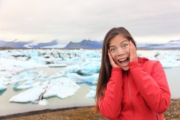 Excited happy woman at glacier lagoon on Iceland