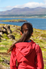 Hiking woman in hardshell jacket in Iceland nature