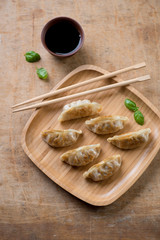 Gyoza dumplings with vegetables and dipping sauce, above view