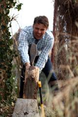 Mann hackt angestrengt Holz in Garten