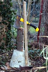 Hackklotz mit Äxten und Holzscheit im Garten