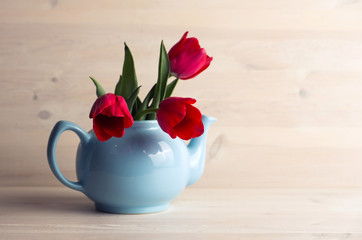 Spring tulips bouquet in teapot over retro wooden background