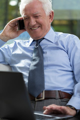Elderly businessman working on laptop