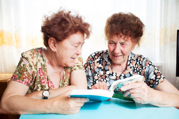 Two seniors reading book