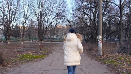 The girl runs winter clothing slowed