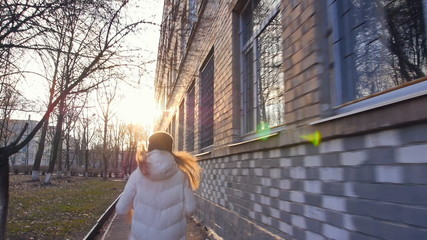 running along the building in winter warm clothes