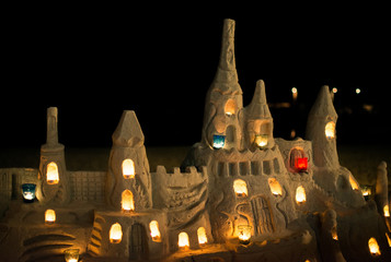 Castle with candles made from sand on the beach.