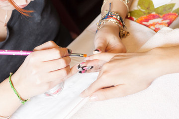 manicurist applying nail extensions