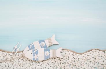 Zwei Fische aus Holz mit Muscheln als Hintergrund blau weiß