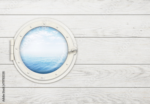 ship window or porthole on white wooden wall with sea or ocean
