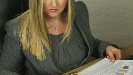 attractive blonde female business executive at graphs & reports