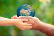 Child and senior holding Earth planet in hands