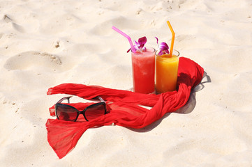 Pair of fruit shakes, red shawl and sunglasses on the tropical b