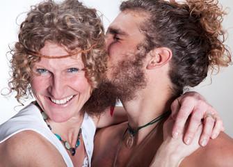 Erwachsener Sohn küsst Mutter liebevoll auf Wange
