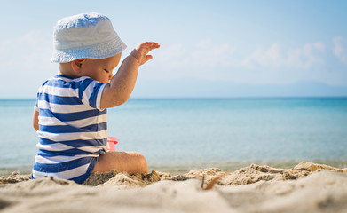 The cute baby boy playing on the beach. Little boy sitting on th