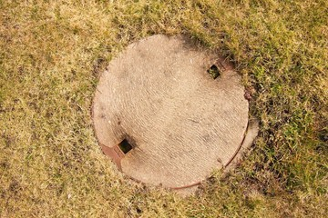 Concrete manhole cover drainage system in cropped grass