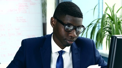 African American with glasses carefully studying business papers